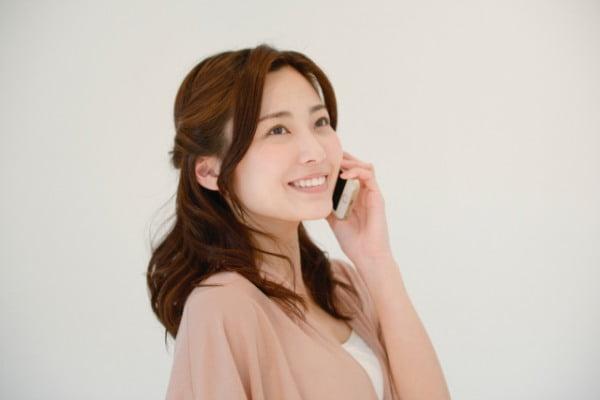 電話をする訪問看護師の女性